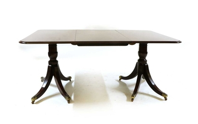 A George lll style mahogany twin pedestal dining table with one leaf