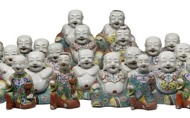 A large collection of Chinese porcelain famille rose figures, late Qing dynasty, with twenty-four figures of Budai painted wearing robes decorated with various designs, including lotus and chrysanthemum blossoms, bats and scrolling leafy vines, and...