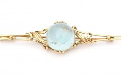 A 14 carat yellow gold bar brooch with topaz. Featuring a round cabochon cut light blue topaz of ca. 23 ct. surrounded by floral motifs. Gross weight: 12.3 g.