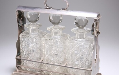 A LATE VICTORIAN SILVER-PLATED THREE-BOTTLE TANTALUS, with b...