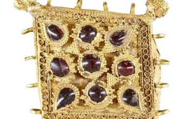 A garnet-set gold pendant element, Iran, 12th century, of diamond shape and box construction, the central field set with nine small garnets within raised frames set with, the base with wire and chain work, the four corners set with faceted ball...