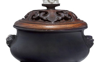 A Chinese porcelain monochrome aubergine glazed censer, 18th century, covered in a rich purple glaze, with moulded lion mask handles, 22.5cm handle to handle, with carved and pierced hardwood cover set with a white jade finial pierced with a dragon...