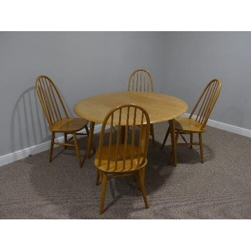 A mid 20thC Ercol style drop leaf oval Dining Table, the top...
