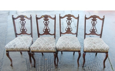 A set of four carved walnut framed side chairs with pierced ...