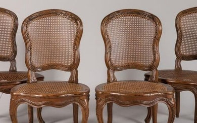 A suite of four walnut chairs, moulded and carved with...