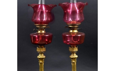 PAIR OF BRASS & CRANBERRY GLASS OIL LAMPS with a brass colum...