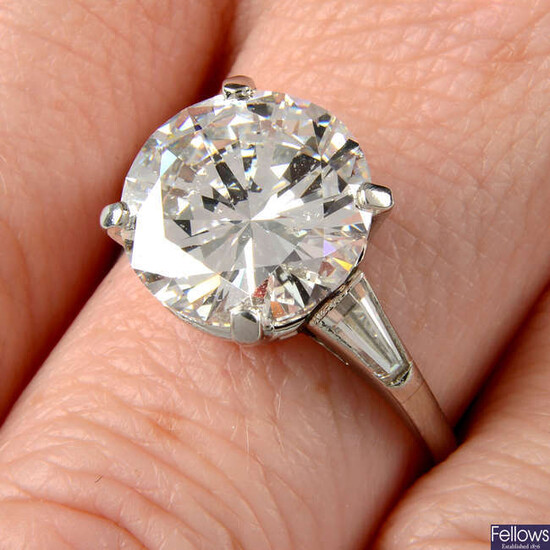 A brilliant-cut diamond single-stone ring, with tapered baguette-cut diamond shoulders.