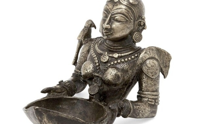 The upper section of a finely moulded brass figure of Meenakshi, the avatar of goddess Pavarti, South India, circa 1700, with parakeet to one shoulder, her hair parted to centre and braided and decorated, her back, chest and arms engraved with...