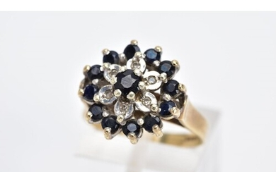 A 9CT GOLD SAPPHIRE AND DIAMOND CLUSTER RING, the large slig...