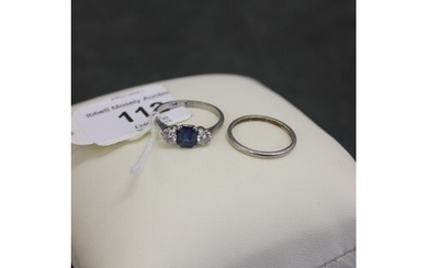 A platinum three stone dress ring, set central sapphire, and...