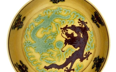 A Chinese small yellow-ground aubergine and green-decorated porcelain saucer dish, Guangxu mark and of the period, incised to the interior with two dragons amongst flames in pursuit of the flaming pearl, painted to the exterior with two kui...