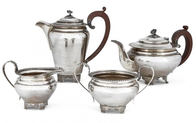 A four-piece silver tea set by Garrard & Co., Birmingham, c.1964, comprising tea pot, coffee pot, sugar and milk jug, each with gadrooned rim and raised on four wing-shouldered paw feet, the pots with wooden handles and flower finials to hinged...