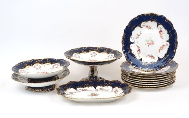 A group of Minton table wares, late 19th Century, of cream and navy blue ground with gilt scrolling highlights to scalloped rims, the centre decorated with floral swags and sprays, comprising a tazza, 12.5cm high, two footed dishes, 23.5cm...