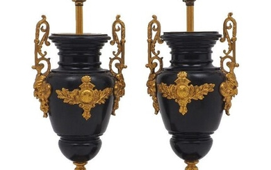 A pair of French slate gilt metal mounted urn-form table lamps, early 20th century, with mask and scroll handles raised on stepped square base set with a plaque depicting a classical scene, 41cm high to fitting