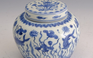 CHINESE BLUE AND WHITE PORCELAIN LIFT-COVER JAR. Carp swimming amidst...