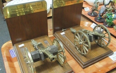Pair of bookends adorned with models of cannons from the bat...