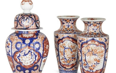 Three Japanese imari porcelain vases, 20th century, the pair painted with panels of birds perched amongst branches, flowerheads and flowering plum blossom, the vase and cover decorated with phoenixes in flight and floral blooms, 30.5cm-41cm high (3)