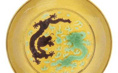 A Chinese imperial porcelain saucer dish, Tongzhi mark and of the period, painted in green and aubergine enamels with two five-clawed dragons encircling a flaming pearl amongst stylised clouds and flames, the underside painted with aubergine grapes...