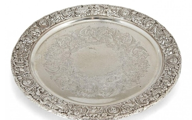 A decorative silver serving plate, London, c.1920, Mappin & Webb, the pierced rim richly decorated with lions, urns and masks to a flat base engraved with foliate and eagle design wreath, the plate raised on three bracket feet, 27.5cm dia., approx...
