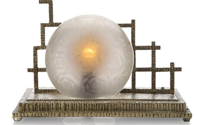 An Art Deco metal table lamp, c.1930, The stepped metal base cast with floral motifs and ribbed edges, the globular frosted shade held by openwork gates, two holes at one end, 16.5 cm high, 24.5 cm long