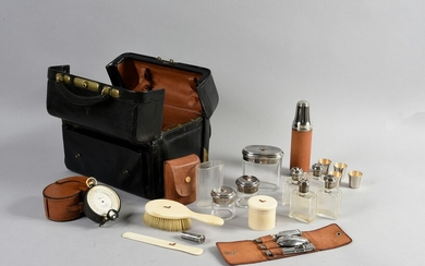 TRAVEL NECESSARY, ALFRED CLARK, LONDON, 1930.A small black morocco case, rectangular in shape, containing a brush, a letter opener, a set of removable cutlery, a glass in its case, a small carafe, four silver-plated goblets, seven silver-mounted...