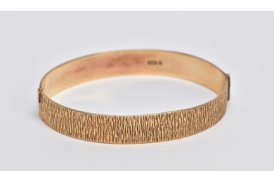 A 9CT GOLD HINGED BANGLE, bark texture to the full bangle, t...