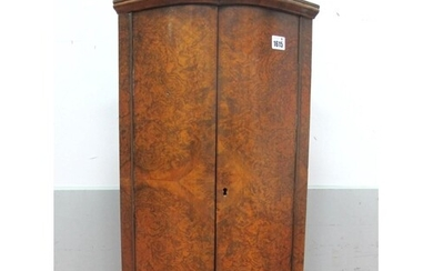 A Burr Walnut Bow Fronted Corner Cupboard, with one internal...