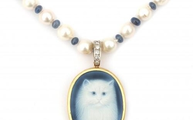 A cameo pendant with a gold mount suspended by a pearl necklace. A cultured pearl necklace with sapphire spacer beads to a 14 karat gold clasp. The agate cameo, depicting a cat has a brilliant set bale. Signed by Hans Ulrich Pauly, Idar-Oberstein...