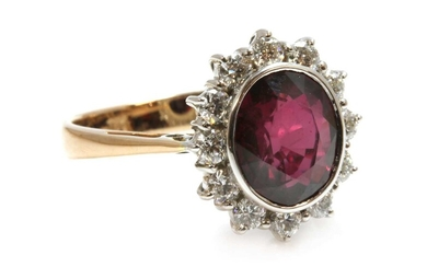A gold ruby and diamond oval cluster ring