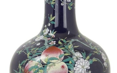 A large Chinese porcelain 'nine peaches' famille rose bottle vase, tianqiuping, Republic period, decorated with a leafy peach tree bearing nine fruit on a dark blue ground, apocryphal Qianlong seal mark to base, 55cm high