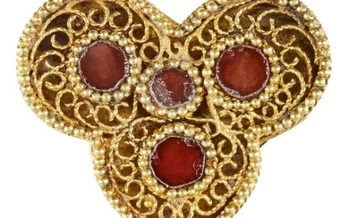 A red glass-set gold element, Iran, 12th-13th century, of trefoil form, the openwork gold filigree face set with four circular glass elements, in raised settings, a solid gold ground beneath, the sides of fine filigree openwork, the reverse with...
