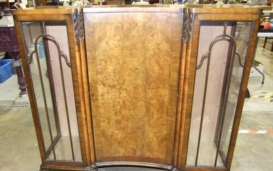 A walnut display cabinet with central concave door, flanked ...