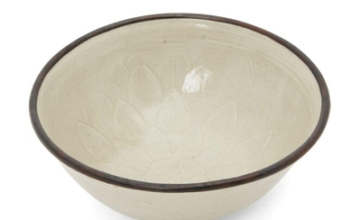 A Chinese Dingyao 'floral' bowl, Northern Song - Jin Dynasty, the interior with a moulded lotus bloom sprouting from several layers of leaves, with allover ivory-white glaze and metal rim, 9.2cm diameter Provenance: Sotheby's Hong Kong, 27 November...