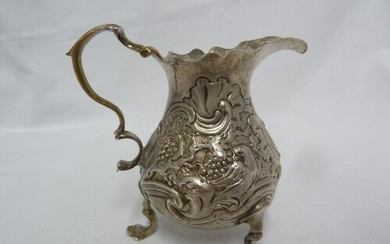 A George II silver cream jug, of baluster form embossed with...