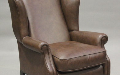 A modern brown leather wing back armchair by Laura Ashley, raised on fluted legs and brass castors