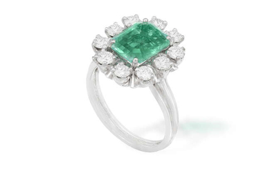 AN EMERALD AND DIAMOND CLUSTER RING The central...