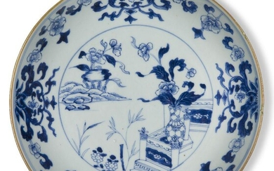 A Chinese porcelain blue and white 'peonies' dish, 18th century, painted with flowering peony blossoms amongst leafy stems issuing from a vase, the outer border decorated with lotus blooms and peony blossoms, 23cm diameter