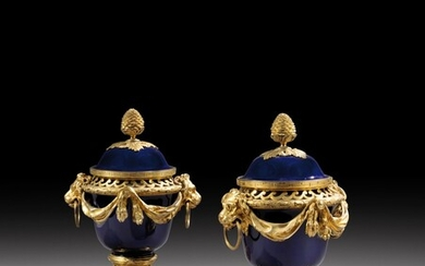 A pair of Louis XVI style gilt-bronze mounted Sèvres porcelain pot-pourri vases with blue ground, after a model by Jean Dulac