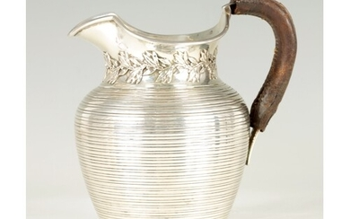 AN EDWARDIAN SILVER HOT MILK JUG with ribbed body and leaf d...