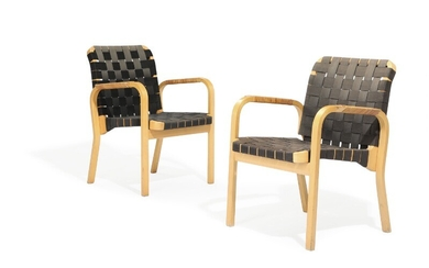 Alvar Aalto: A pair of birch armchairs, seat and back with black canvas girths, armrests...