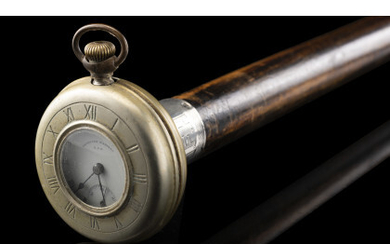 """An early 20th-century beechwood walking stick with silvered metal handle enclosing a silver """"American Waltham USA"""" pocket watch (1920 circa).…Read more"""