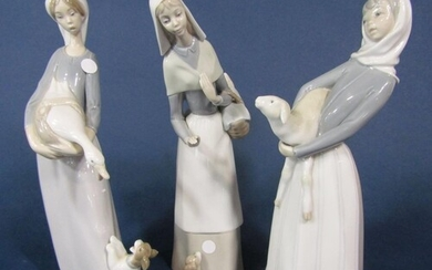 Two Lladro figures of a girl holding a lamb and a woman with...