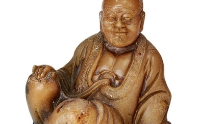A Chinese soapstone carving of a Luohan, 18th/19th, century, finely carved in a seated pose with serene expression, his robes finely incised with decorative motifs and inset with three coral and turquoise beads, the underside incised with clouds...