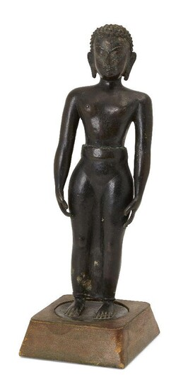 A Jain bronze figure of Tirthankara, South India, 17th century or earlier, on a flat, round base, standing with arms at his side in the tadasana pose, a serene expression on his face and with hair in tight sculpted curls, on a square wood base...