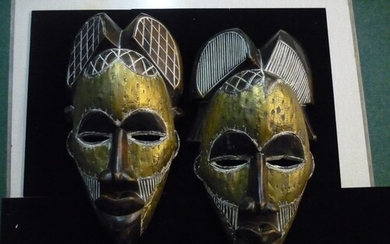 A pair of African tribal masks with engraving to the hairpie...