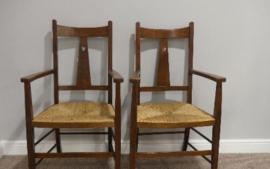 A pair of Arts and Crafts oak Carver Chairs, with rush seats...