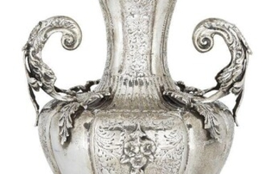 A 19th century twin-handled Continental vase, apparently unmarked, assumed silver, the lobed baluster-shaped body applied with twinned leaves and floral swags to a fluted neck with shaped rim, the vase raised on a lobed circular foot chased with...
