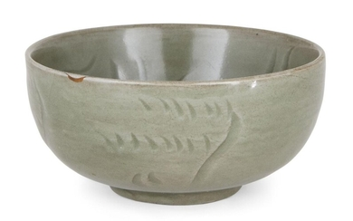 A Chinese Longquan celadon 'lotus' bowl, Ming dynasty, the interior decorated with an incised lotus blossom amongst wavy flourishes, the exterior with further incised abstract decoration, covered in an allover celadon glaze, 14cm diameter...