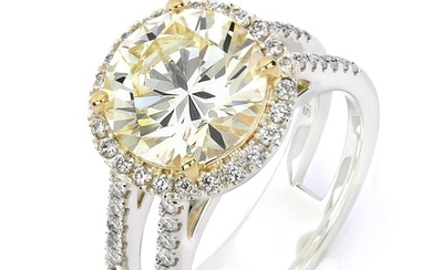 A DOUBLE SHANK HALO DIAMOND ENGAGEMENT RING A Double Shank H...