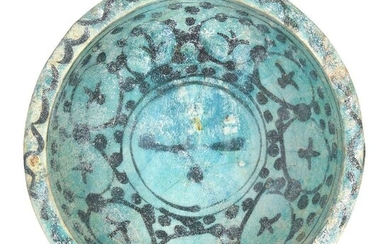 A Kashan turquoise-glazed pottery bowl, Iran, 12th century, underglaze painted in black with a series of circles containing abstract motifs to centre well, o a ground of black dots, 22cm diameter Provenance: Private collection London since 1968